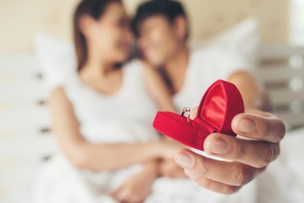 Hombre joven que trae caja de anillo para su novia en su casa