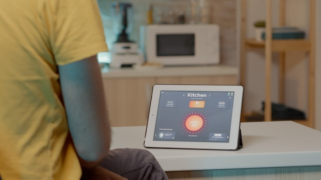 Hombre joven que usa la aplicación de casa inteligente con comando de voz para encender la luz con tableta digital