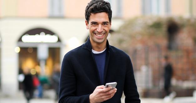 Hombre joven que usa un teléfono inteligente al aire libre
