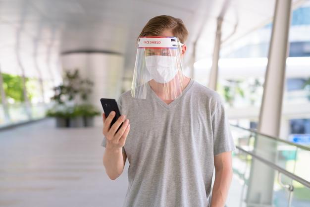 Hombre joven que usa el teléfono con máscara y protector facial para protegerse del brote de virus corona en la ciudad al aire libre