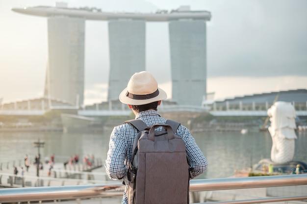 Hombre joven que viaja con la mochila y el sombrero por la mañana, solo viajero asiático visita en el centro de la ciudad de singapur. punto de referencia y popular para las atracciones turísticas. concepto de viaje de asia