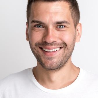 Hombre joven de rastrojo sonriente en camiseta blanca contra la pared lisa