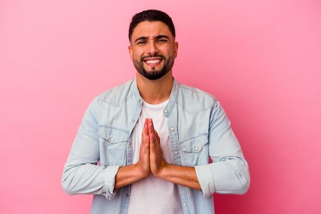 Hombre joven de raza mixta aislado sobre fondo rosa tomados de la mano en oración cerca de la boca, se siente seguro.