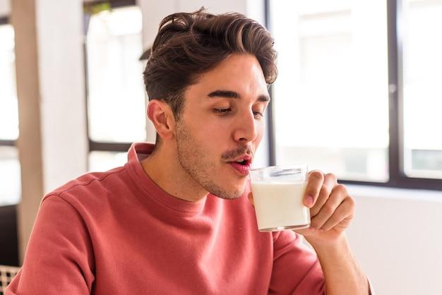 Hombre joven de raza mixta bebiendo leche para el desayuno