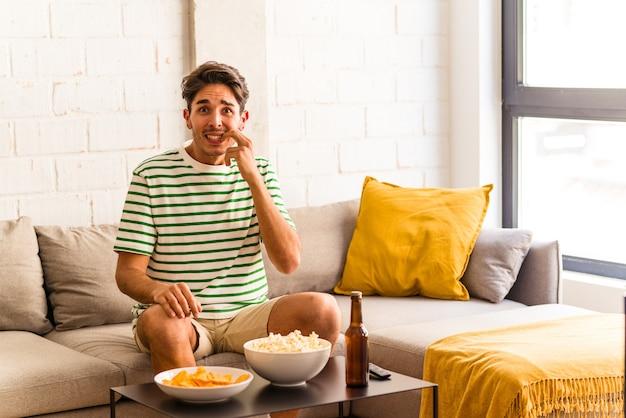 Hombre joven de raza mixta comiendo palomitas de maíz sentado en el sofá mordiéndose las uñas, nervioso y muy ansioso.