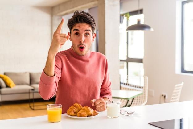 Hombre joven de raza mixta desayunando en una cocina por la mañana con una idea, concepto de inspiración.