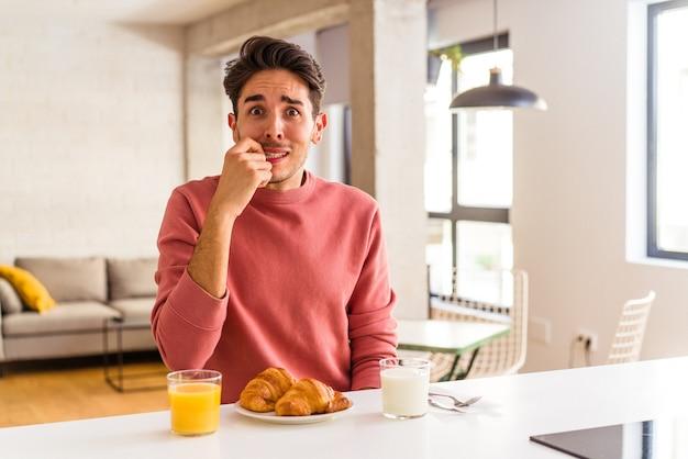 Hombre joven de raza mixta desayunando en una cocina en la mañana mordiéndose las uñas, nervioso y muy ansioso.