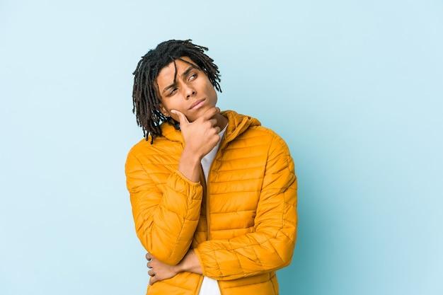 Hombre joven de raza mixta pensando y mirando hacia arriba, siendo reflexivo, contemplando, teniendo una fantasía.