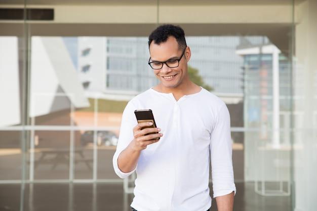 Hombre joven de la raza mixta que manda un sms en el teléfono, sonriendo. vista frontal