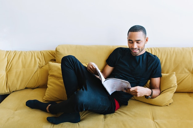 El hombre joven se relaja en el sofá en la ropa de casa. chico guapo leyendo una revista con entusiasmo. confort en el hogar, descanso después del trabajo.
