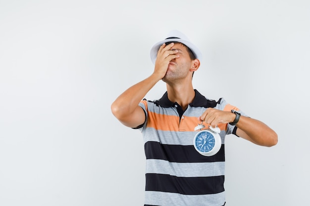 Hombre joven con reloj despertador en camiseta y sombrero y mirando olvidadizo