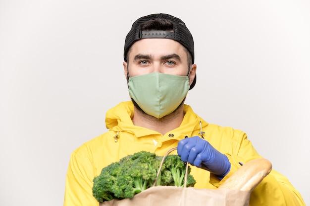 Hombre joven en respirador protector en la cara y guantes en las manos con bolsa de papel con verduras frescas y pan del supermercado
