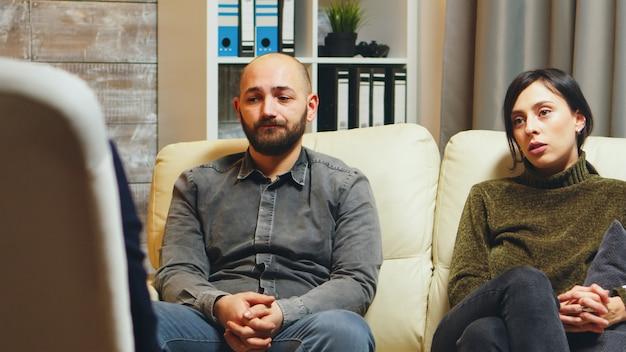 Hombre joven respirando pesadamente sentado en el sofá con su esposa en terapia de pareja hablando de su relación.