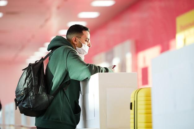 Hombre joven en ropa casual, anteojos y máscara protectora de pie junto al mostrador de registro en el salón del aeropuerto y esperando a la recepcionista