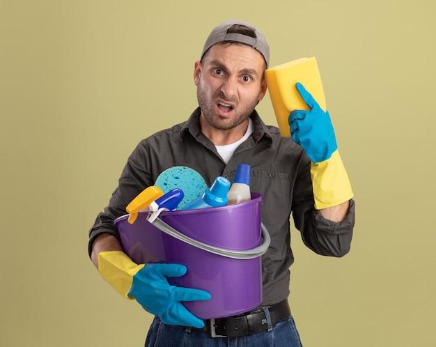 Hombre joven con ropa casual y gorra en guantes de goma sosteniendo un balde con herramientas de limpieza y una esponja que parece confundido y disgustado de pie sobre la pared verde