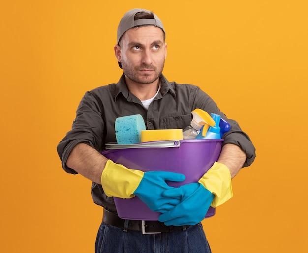 Hombre joven con ropa casual y gorra en guantes de goma sosteniendo un balde con herramientas de limpieza mirando hacia arriba confundido y disgustado de pie sobre la pared naranja