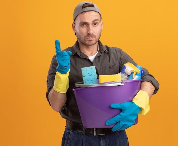 Hombre joven con ropa casual y gorra en guantes de goma sosteniendo un balde con herramientas de limpieza mirando con expresión de confianza mostrando el dedo índice de pie sobre la pared naranja