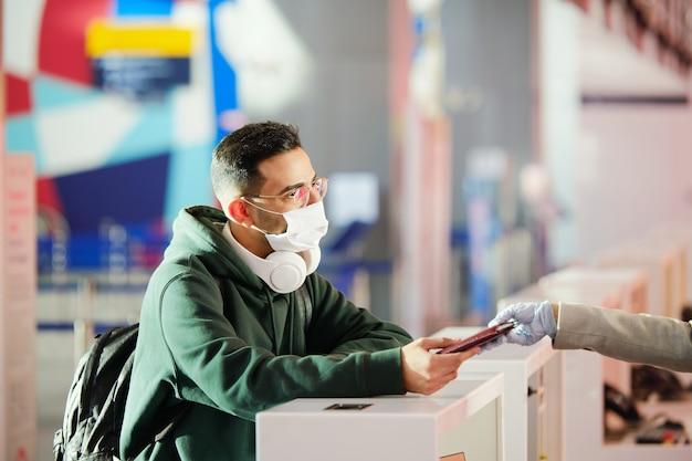 Hombre joven en ropa casual y máscara protectora que recupera su pasaporte después del registro antes del vuelo en el mostrador de facturación en el aeropuerto