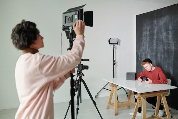 Hombre joven en ropa casual preparando la cámara de video antes de disparar mientras está de pie en el estudio frente a un vlogger masculino