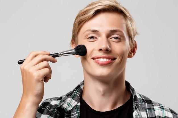 Hombre joven rubio hermoso divertido que lleva la camisa a cuadros casual con el cepillo del maquillaje