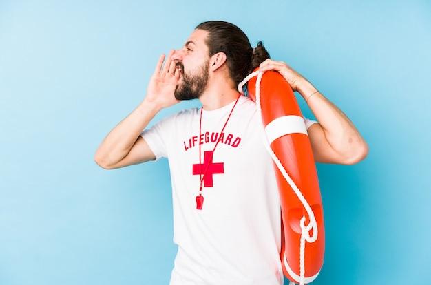 El hombre joven del salvavidas que sostenía un flotador del rescate aisló gritar y sostener la palma cerca de boca abierta.