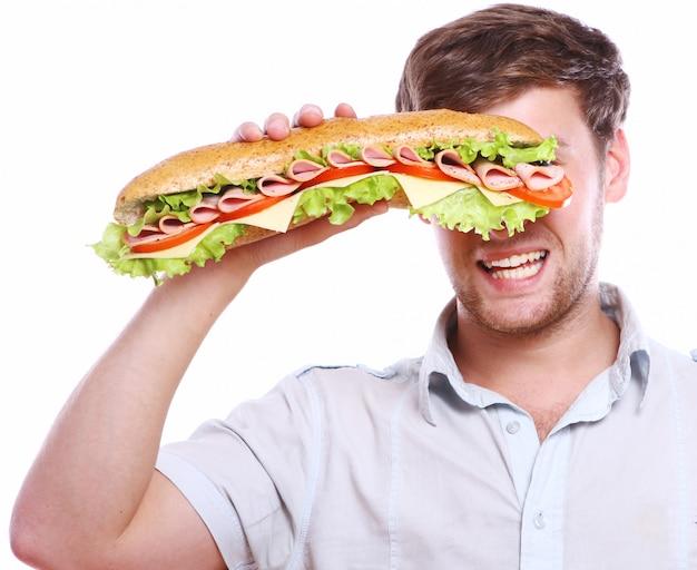 Hombre joven con sándwich grande