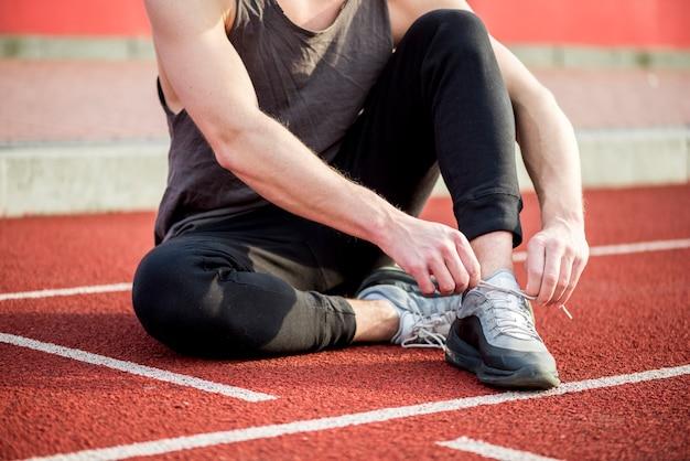Hombre joven sano sentado en la pista de atletismo atando su cordón