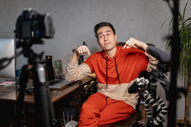 Hombre joven sentado en el escritorio hablando con la cámara. chico grabando un video con equipos profesionales. vlog, concepto de autónomo.