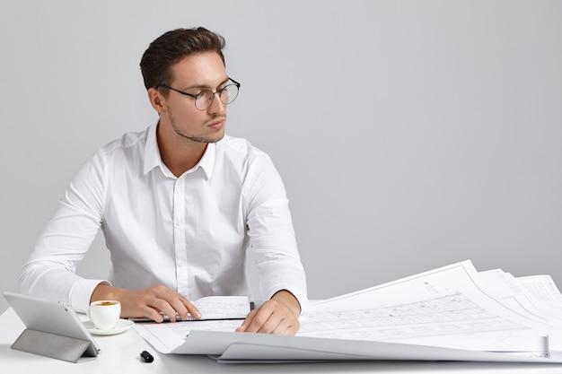Hombre joven sentado en el escritorio y hacer trámites