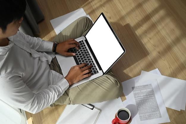 Un hombre joven está sentado en el piso en casa y usando una computadora portátil