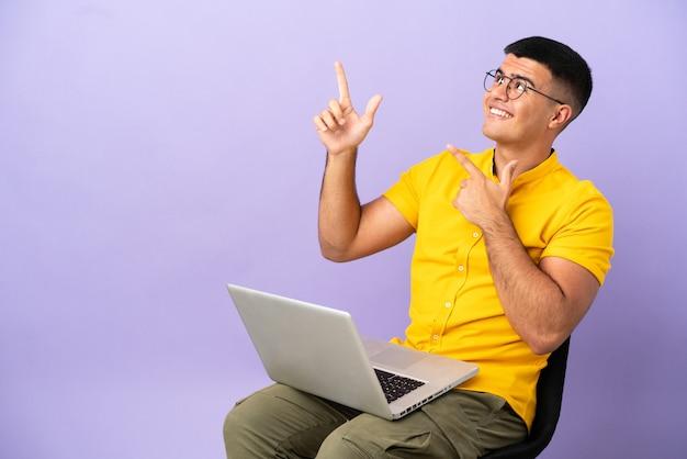 Hombre joven sentado en una silla con portátil apuntando con el dedo índice una gran idea