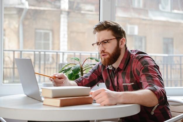 Hombre joven serio cerca de libros usando la computadora portátil.