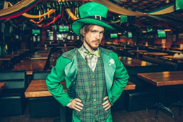 Hombre joven serio y concentrado en traje verde está solo en el pub. él toma las manos en las caderas y mira. el tipo usa el disfraz de san patricio.