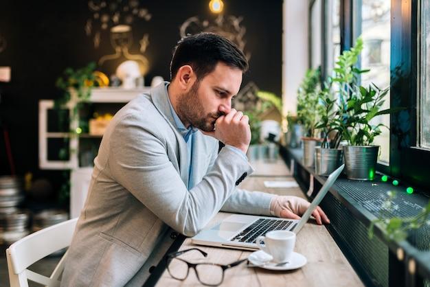 Hombre joven serio con la mano vendada que mira el ordenador portátil mientras que se sienta en el café.