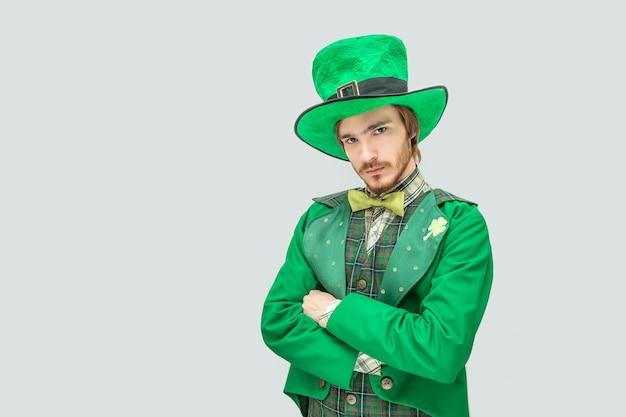 Hombre joven serio y molesto en traje verde. él cruzó las manos. pelirroja es infeliz. aislado en gris