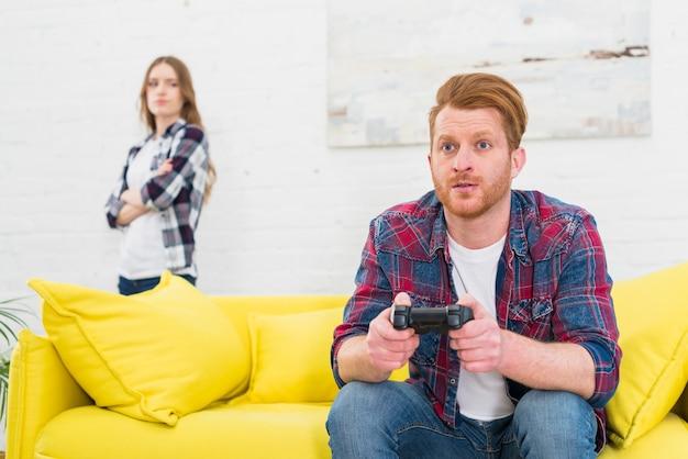 Hombre joven serio que juega al juego con el controlador de video con su novia de pie en el fondo