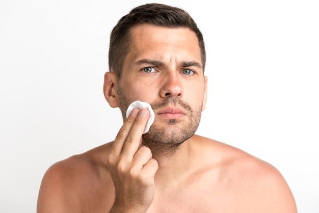 Hombre joven serio que limpia su cara contra el fondo blanco