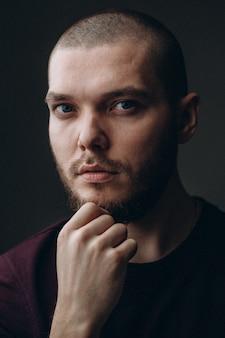 Hombre joven serio que mira en un marco en un espacio gris. calvo con barba