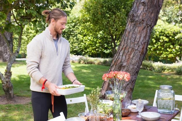 Hombre joven serio que sirve comida al aire libre
