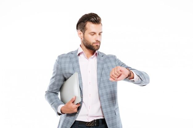 Hombre joven serio que sostiene el ordenador portátil que mira el reloj.