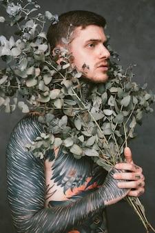 Hombre joven serio con tatuaje en su cuerpo sosteniendo ramas de planta debajo de su cara