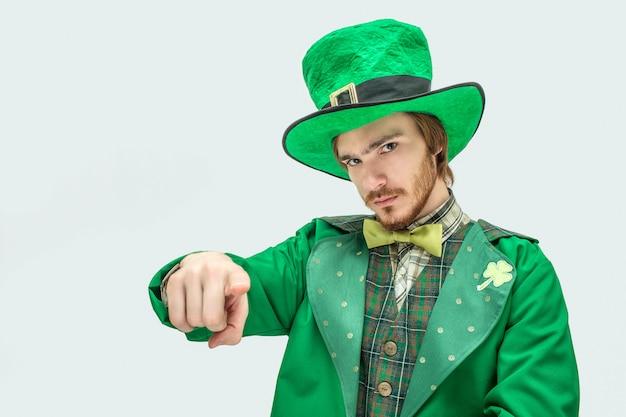 Hombre joven serio en traje verde punto directamente en la cámara. lleva el traje de san patricio. aislado sobre fondo gris