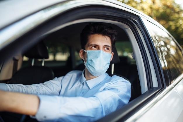 El hombre joven se sienta detrás del volante en el coche con una máscara médica estéril. distancia social, concepto de prevención y tratamiento de propagación de virus.