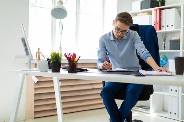 Un hombre joven se sienta en la oficina en un escritorio de la computadora y escribe en un cuaderno.