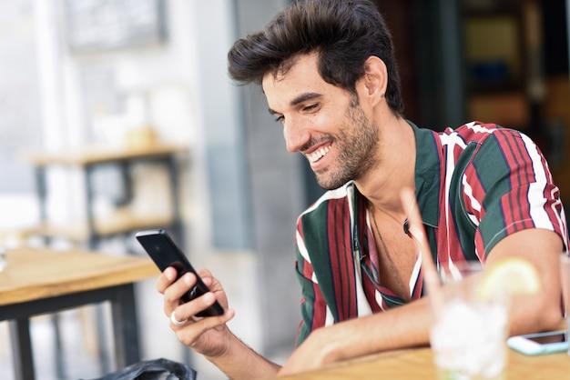 Hombre joven con smartphone en un café urbano.