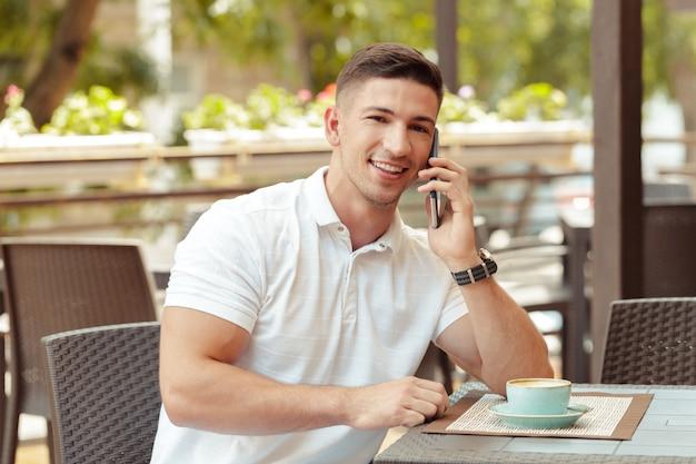 Hombre joven con smartphone en café