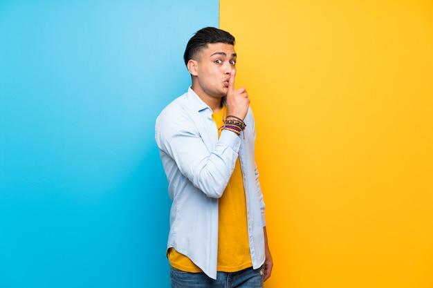 Hombre joven sobre aislado colorido haciendo gesto de silencio