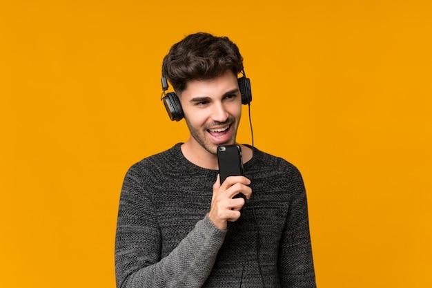 Hombre joven sobre aislado usando el móvil con auriculares y cantando