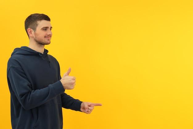 Hombre joven sobre fondo amarillo, espacio para texto.