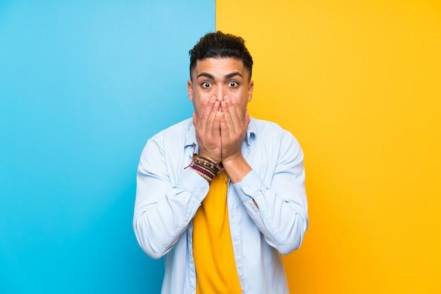 Hombre joven sobre fondo colorido aislado con expresión facial sorpresa